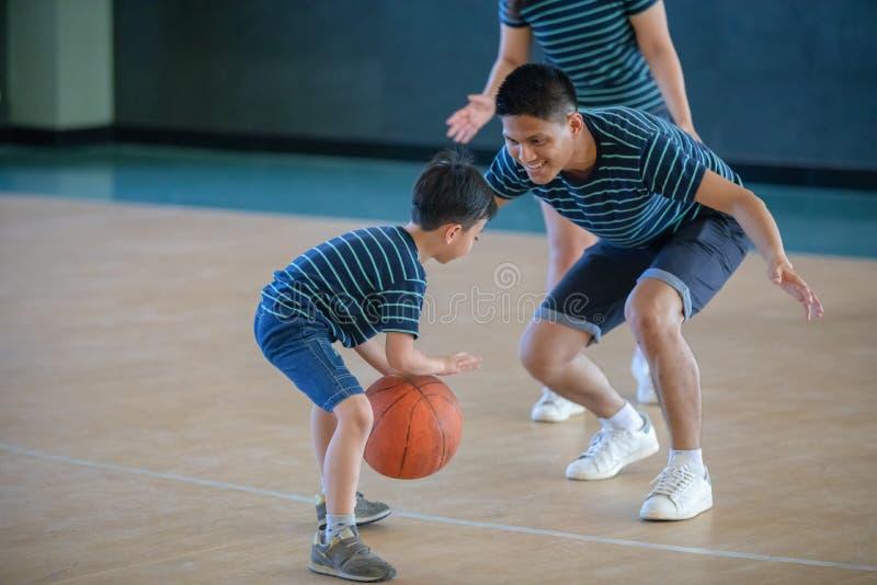 Familia asiática que juega al baloncesto junto Familia feliz que pasa el tiempo libre junto el día de fiesta imagen de archivo