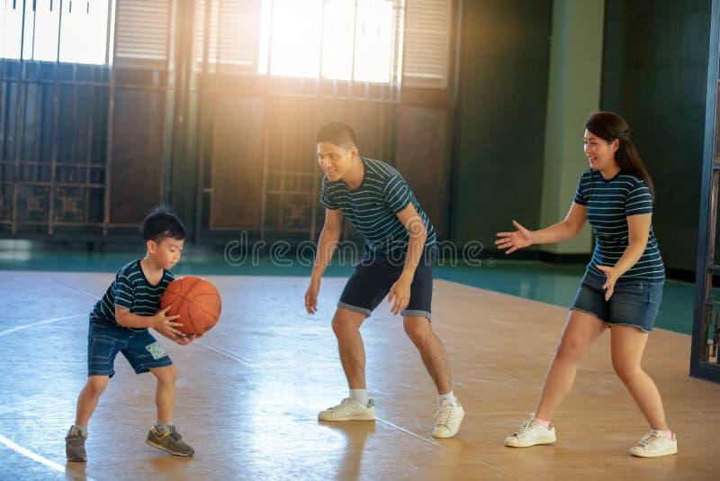 Familia asiática que juega al baloncesto junto Gasto feliz de la familia foto de archivo libre de regalías