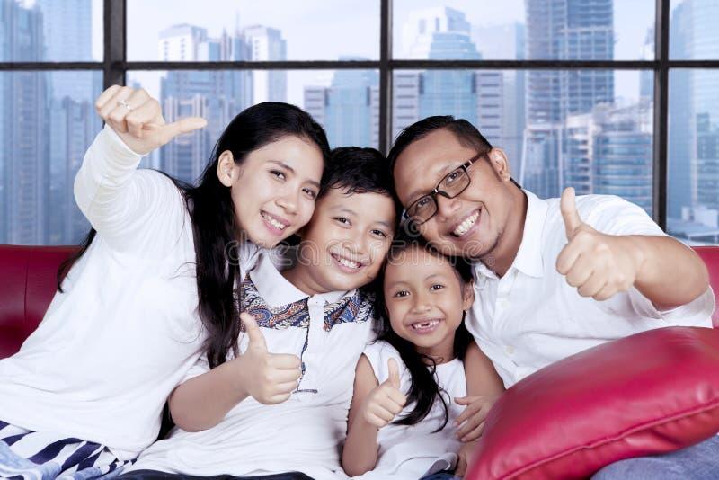Familia asiática que muestra los pulgares para arriba en el apartamento imagenes de archivo