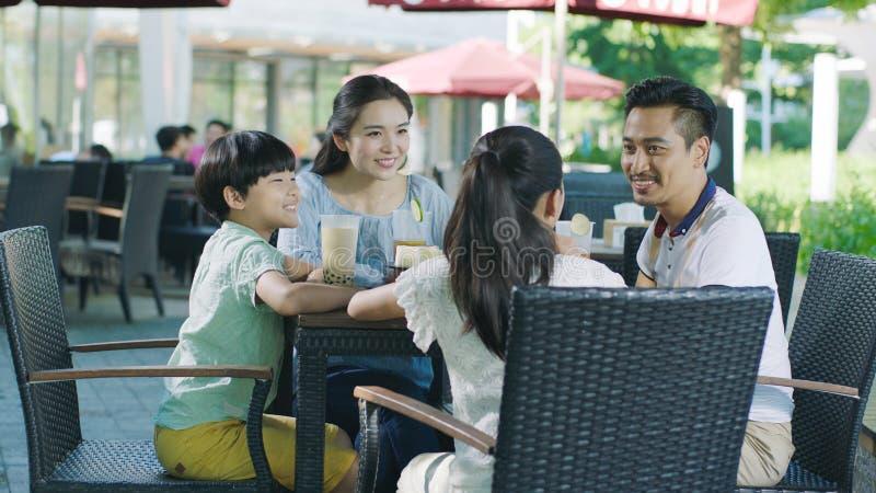 Familia asiática que sonríe, comiendo y bebiendo al aire libre en la tabla del streetside foto de archivo