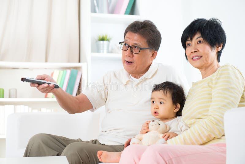 Familia asiática que ve la TV fotos de archivo