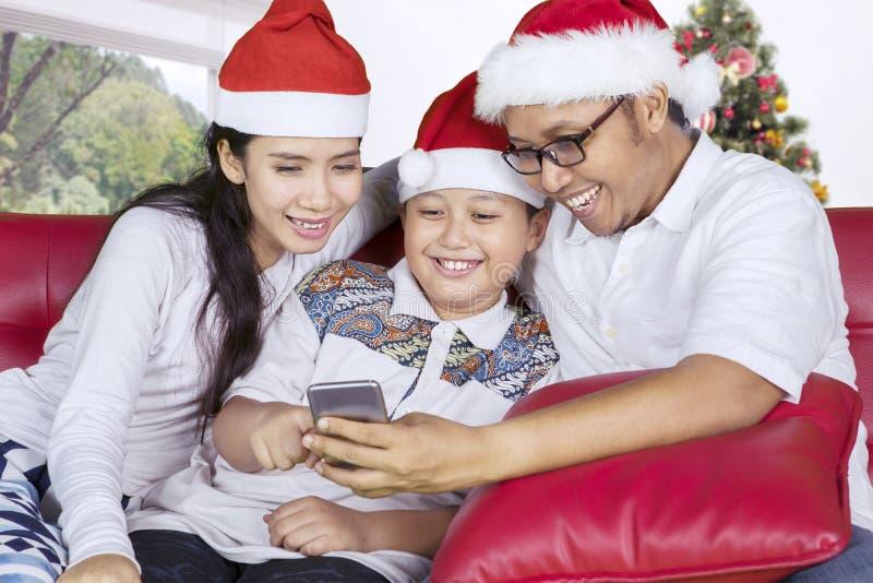 Familia asiática usando un smartphone cerca del árbol de navidad foto de archivo