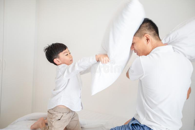 Familia asi?tica feliz con el hijo en casa en el dormitorio que juega y que r?e fotos de archivo