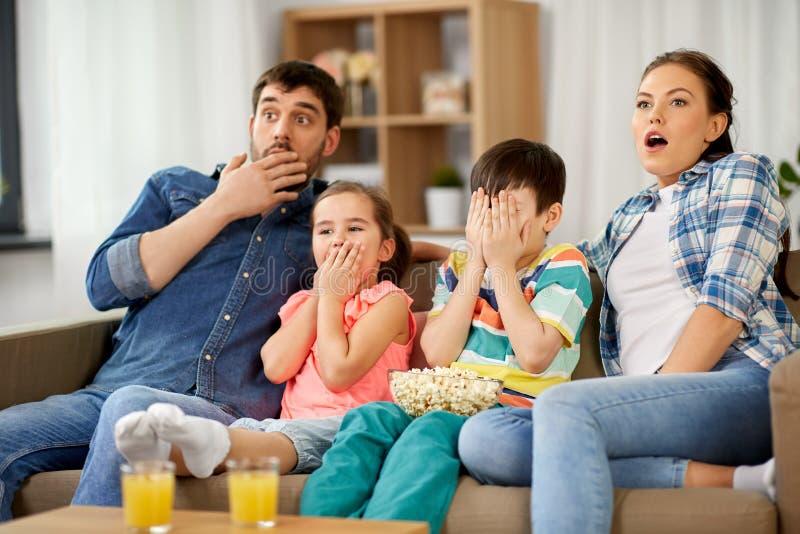 Familia asustada con horror de observación de las palomitas en la TV foto de archivo libre de regalías