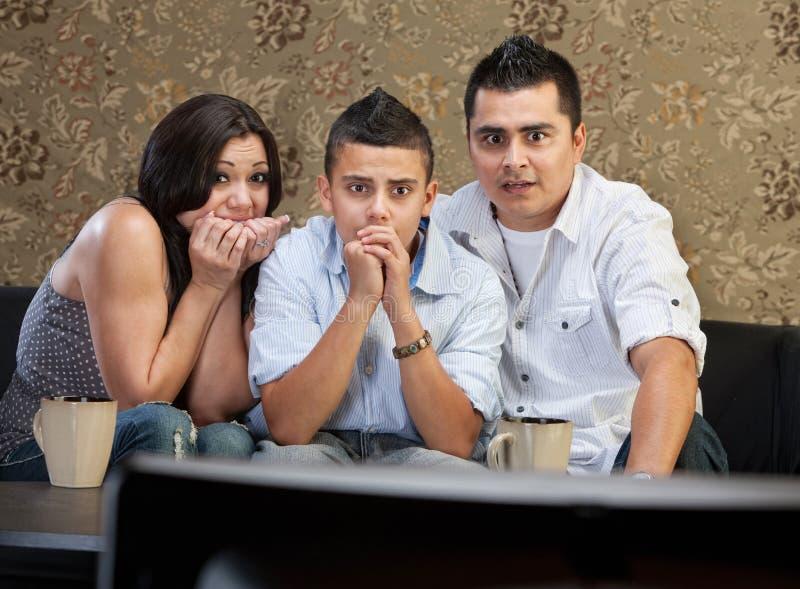 Familia asustada que ve la TV imagen de archivo