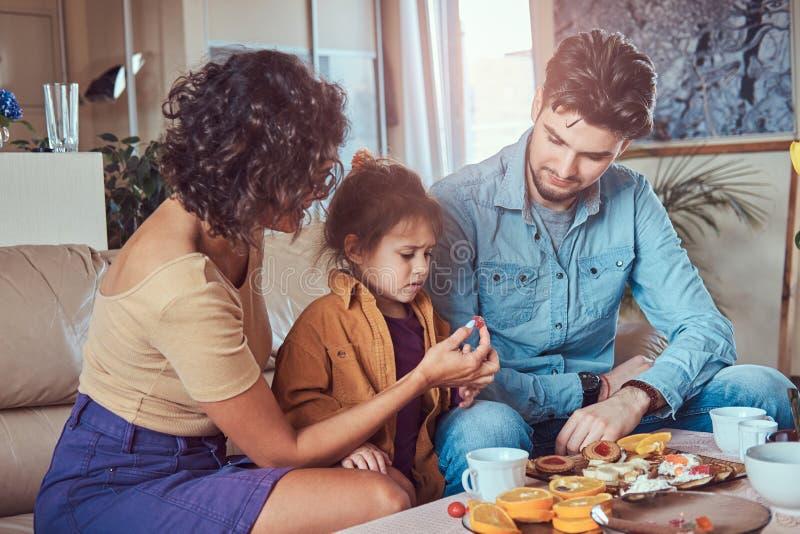 Familia atractiva joven del desayuno de la familia que desayuna en casa que se sienta en un sofá imagenes de archivo