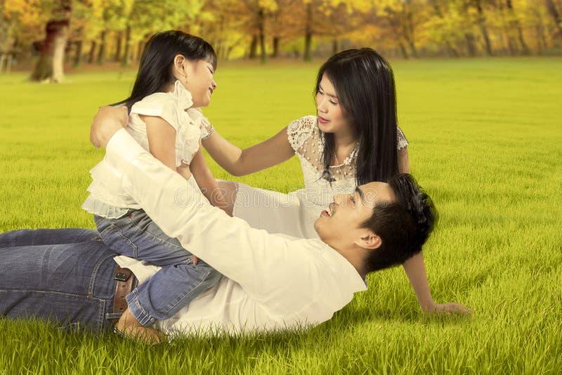Familia atractiva que juega en el parque del otoño fotos de archivo libres de regalías