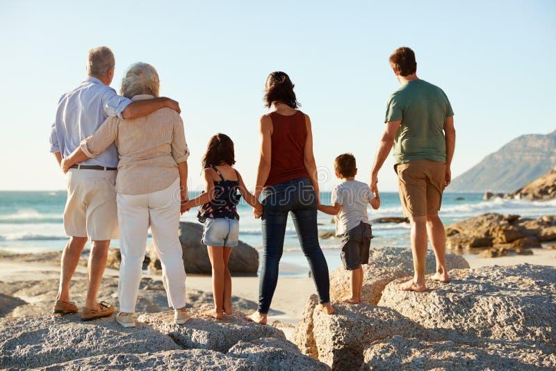 Familia blanca de tres generaciones en un soporte de la playa que lleva a cabo las manos, admirando la visión, visión integral, t foto de archivo