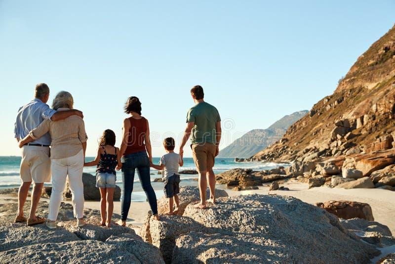 Familia blanca de tres generaciones en un soporte de la playa que lleva a cabo las manos, admirando la visión, visión integral, t imagenes de archivo