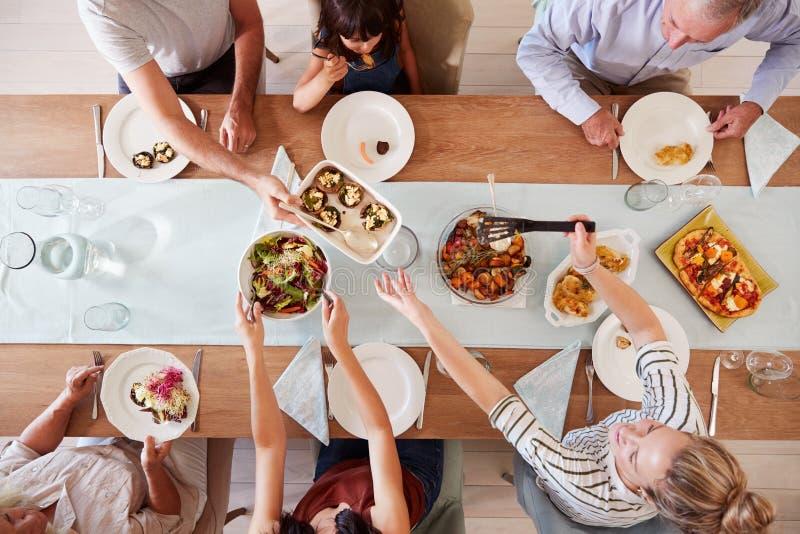 Familia blanca de tres generaciones que se sienta en una tabla de cena junto que sirve una comida, visión de arriba fotos de archivo libres de regalías