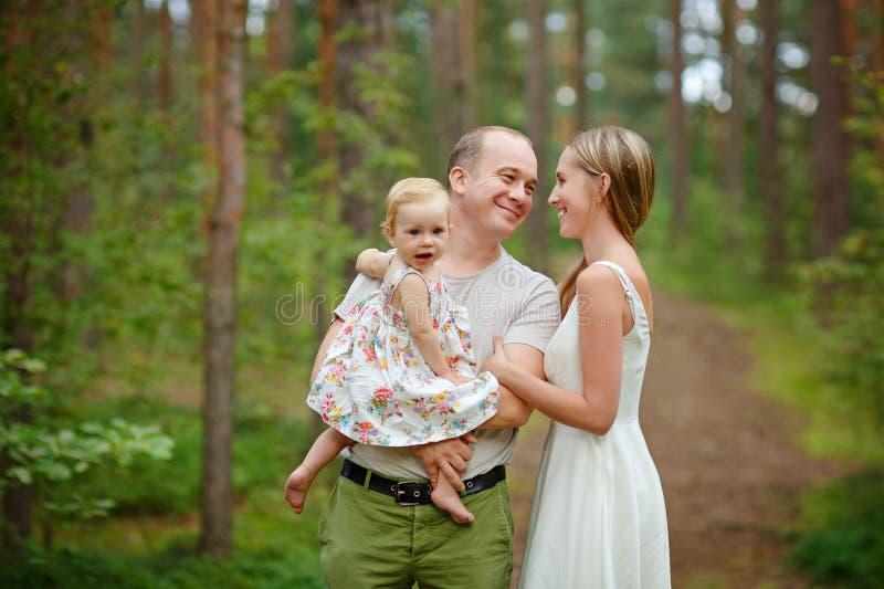 Familia - blonde de la madre, del padre y de la hija en un bosque a del verano imagen de archivo