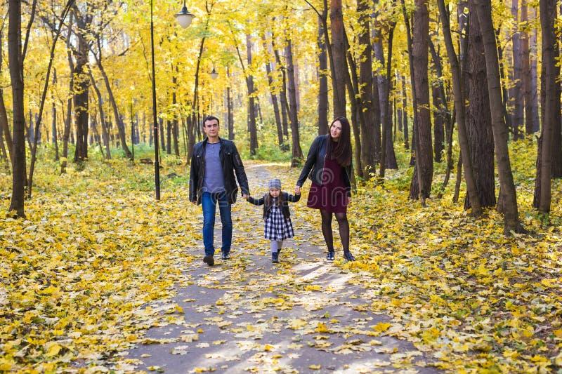 Familia, caída, concepto de la gente - familia joven de la raza mixta que camina en parque encendido en día del otoño foto de archivo libre de regalías