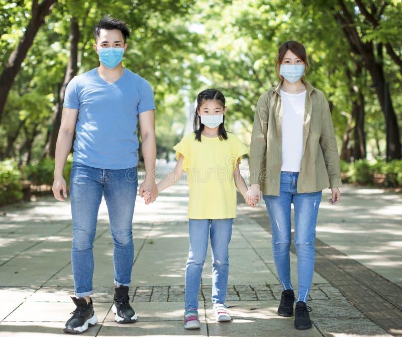 Familia caminando y usando máscara durante la emergencia del coronavirus foto de archivo