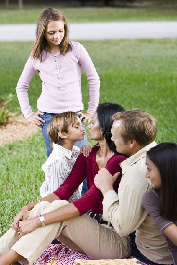 Familia cariñosa de cinco junto en parque foto de archivo