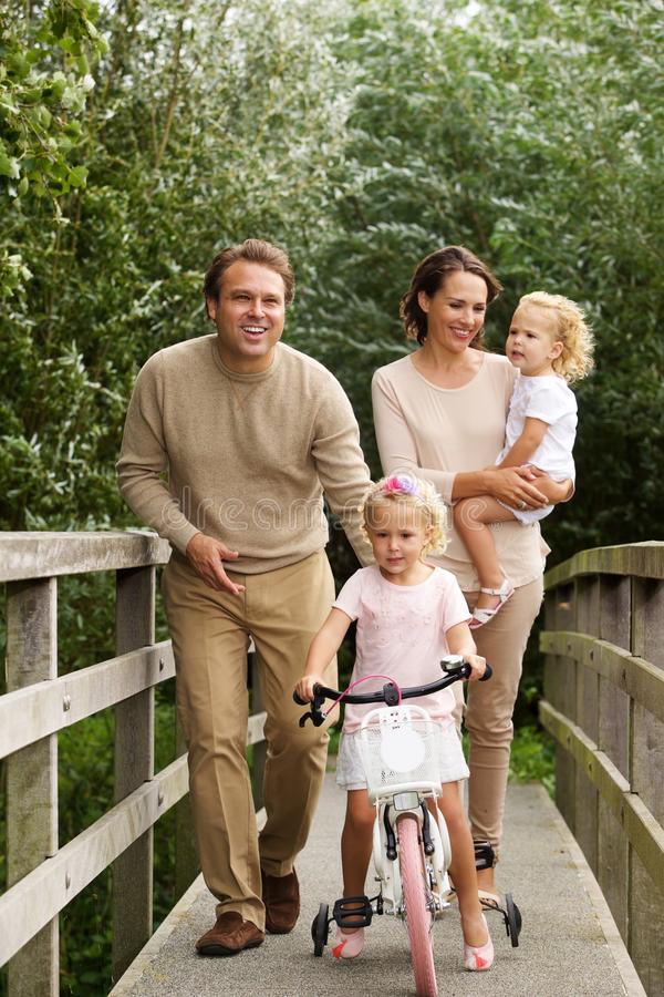 Familia cariñosa en el pequeño puente en el parque fotografía de archivo libre de regalías