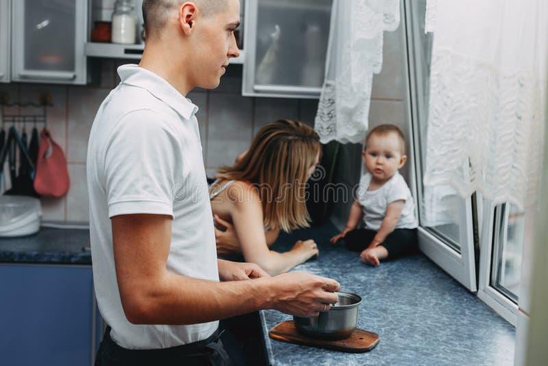 Familia cariñosa en la cocina Papá que cocina la cena mientras que mamá que juega w fotografía de archivo
