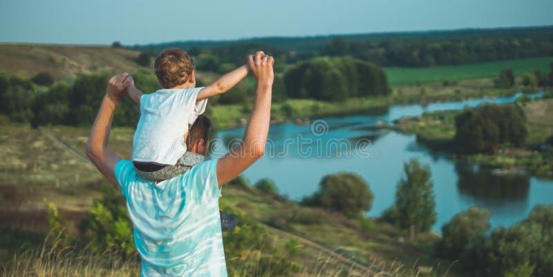 Familia cariñosa Engendre y su bebé del hijo que juega y que abraza al aire libre Papá e hijo felices al aire libre Concepto de d imagen de archivo