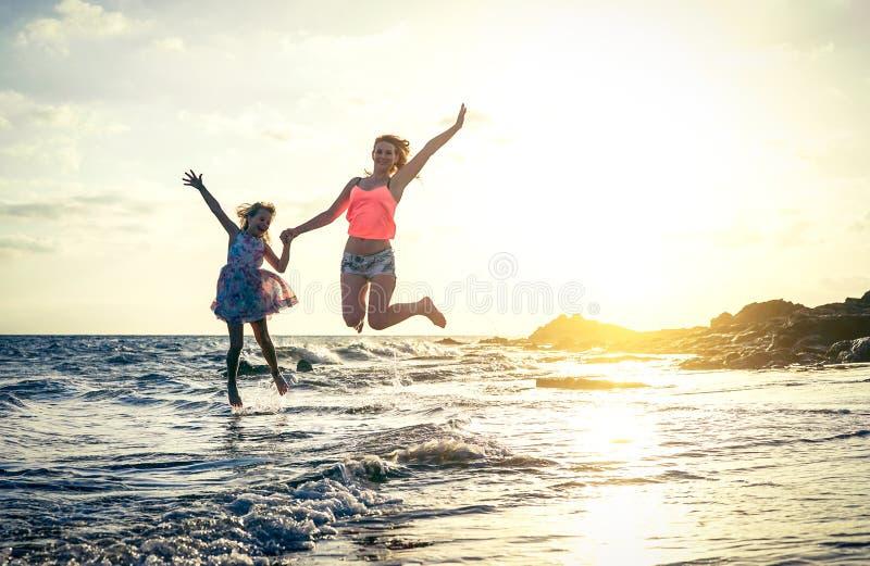 Familia cariñosa feliz de la madre y de la hija que saltan en el agua en la puesta del sol en la playa - mamá con su niño que se  foto de archivo