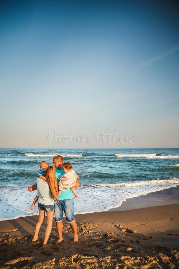 Familia cariñosa feliz joven con los pequeños niños que se divierten en la playa junto cerca del océano, concepto de familia feli imagen de archivo libre de regalías