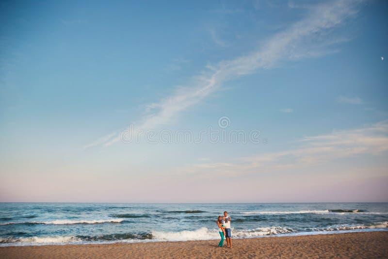 Familia cariñosa feliz joven que abraza en la playa junto cerca del océano, concepto de familia feliz de la forma de vida fotos de archivo