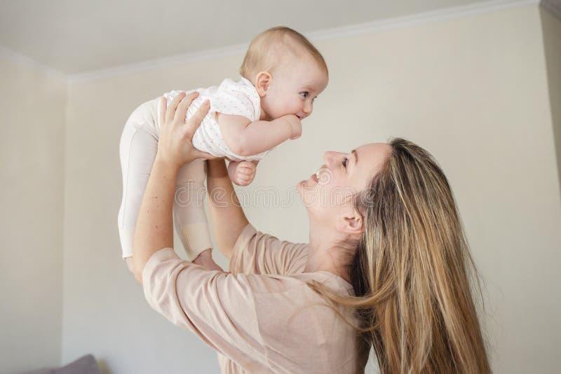 Familia cariñosa feliz madre que juega con su bebé interior Hija hoding y sonrisa de la mamá imagenes de archivo