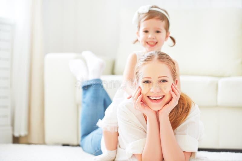 Familia cariñosa feliz madre y niño que juegan la mentira en el piso fotografía de archivo