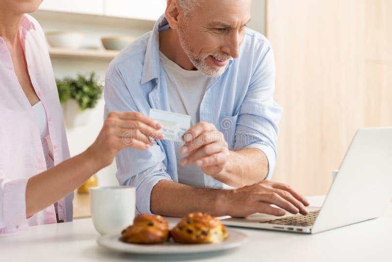 Familia cariñosa madura feliz de los pares usando el ordenador portátil que sostiene la tarjeta de crédito imágenes de archivo libres de regalías