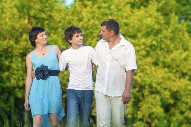 Familia caucásica de tres que tienen un paseo junto en el parque abrazado imagen de archivo