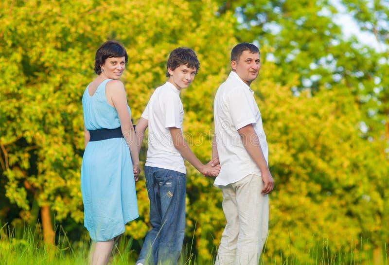 Familia caucásica del tiempo de gasto tres junto abrazado en parque del verano fotografía de archivo