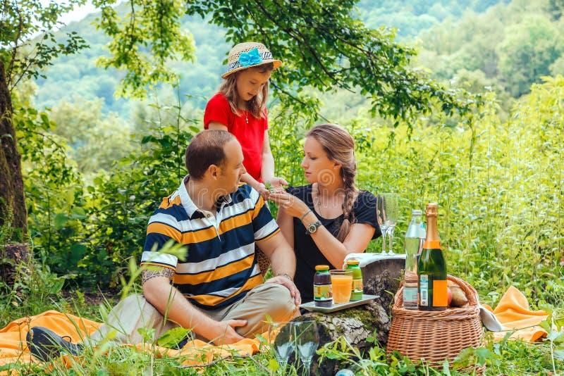 Familia caucásica feliz joven de padre, de madre y de hija teniendo comida campestre el vacaciones en bosque de la montaña del ve imagenes de archivo
