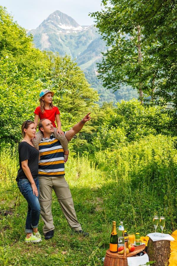 Familia caucásica feliz joven de tres personas que tienen comida campestre en bosque de la montaña del verano en fondo del pico d fotografía de archivo libre de regalías