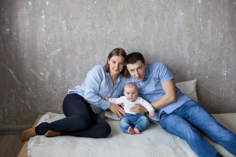 Familia caucásica joven feliz que miente en cama imagenes de archivo