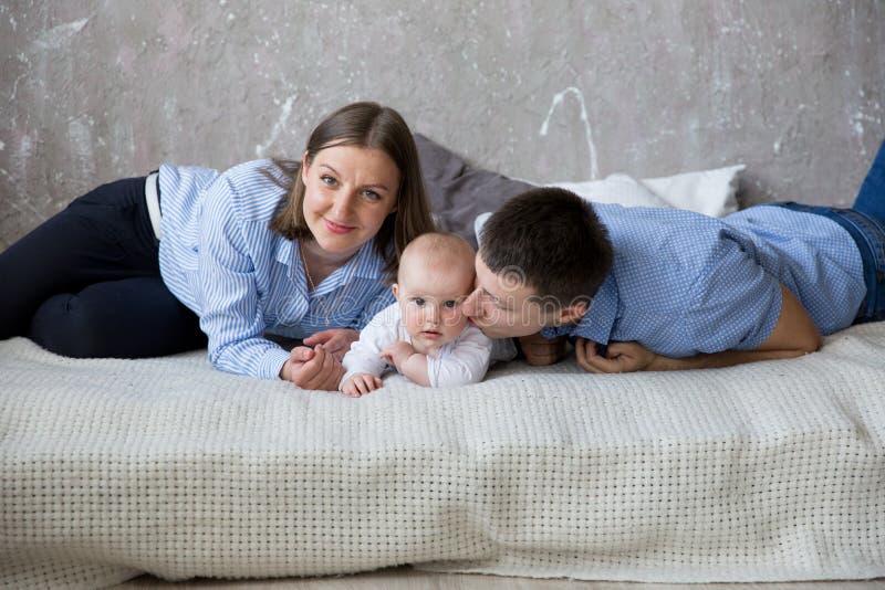 Familia caucásica joven feliz que miente en cama fotos de archivo libres de regalías