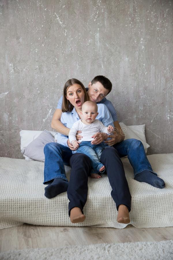 Familia caucásica joven feliz que se sienta en cama foto de archivo