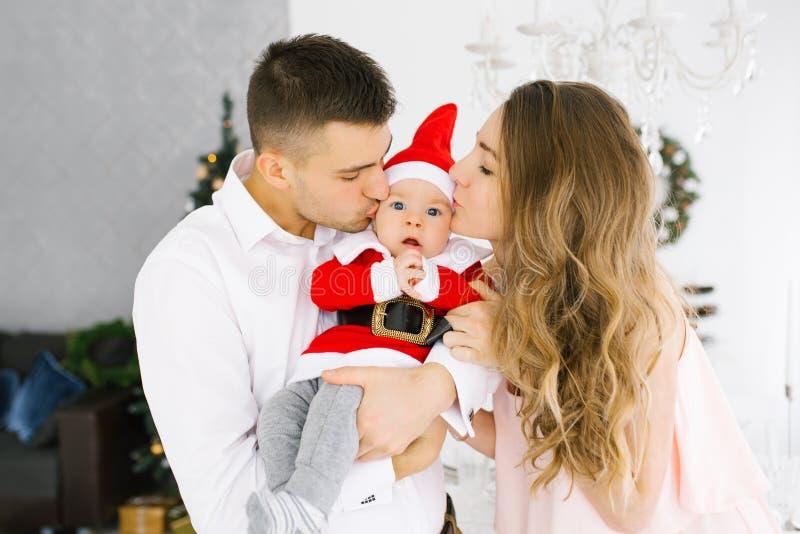 Familia celebra Navidad en casa en el salón cerca del árbol de Navidad Feliz mamá, papá e hijo disfrutan sus vacaciones juntos fotografía de archivo libre de regalías