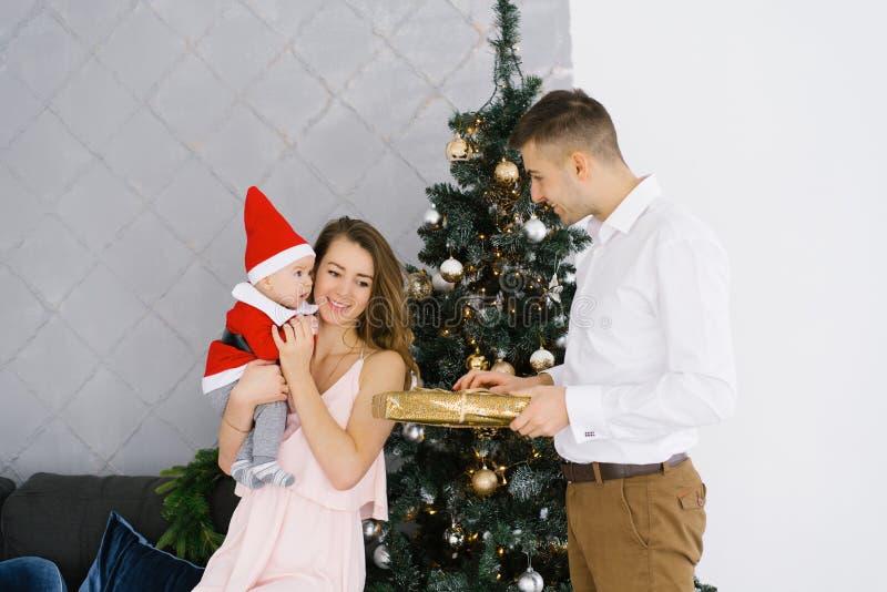 Familia celebra Navidad en casa en el salón cerca del árbol de Navidad Feliz mamá, papá e hijo disfrutan sus vacaciones juntos imagenes de archivo