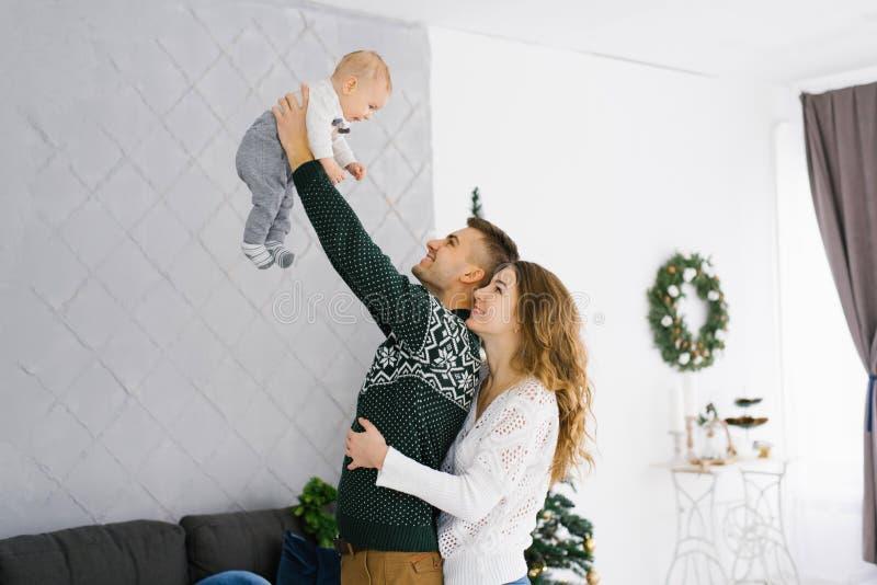 Familia celebra Navidad en casa en el salón cerca del árbol de Navidad Feliz mamá, papá e hijo disfrutan sus vacaciones juntos fotografía de archivo