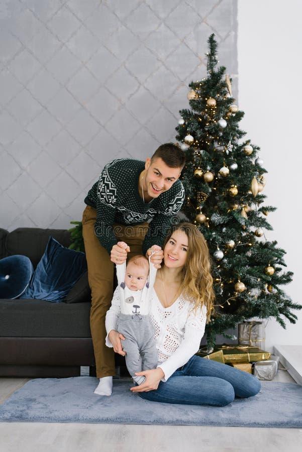 Familia celebra Navidad en casa en el salón cerca del árbol de Navidad Feliz mamá, papá e hijo disfrutan sus vacaciones juntos foto de archivo