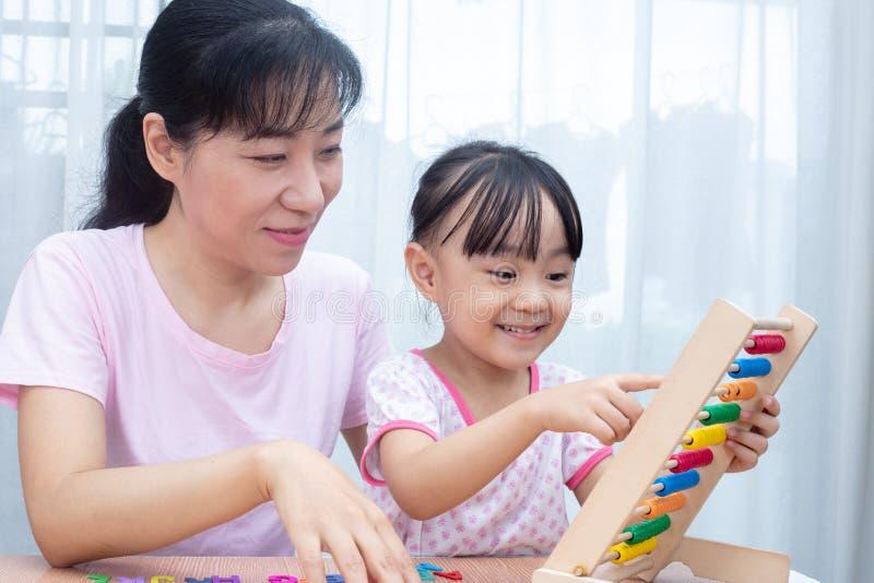 Familia china asiática feliz que juega el ábaco colorido junto foto de archivo
