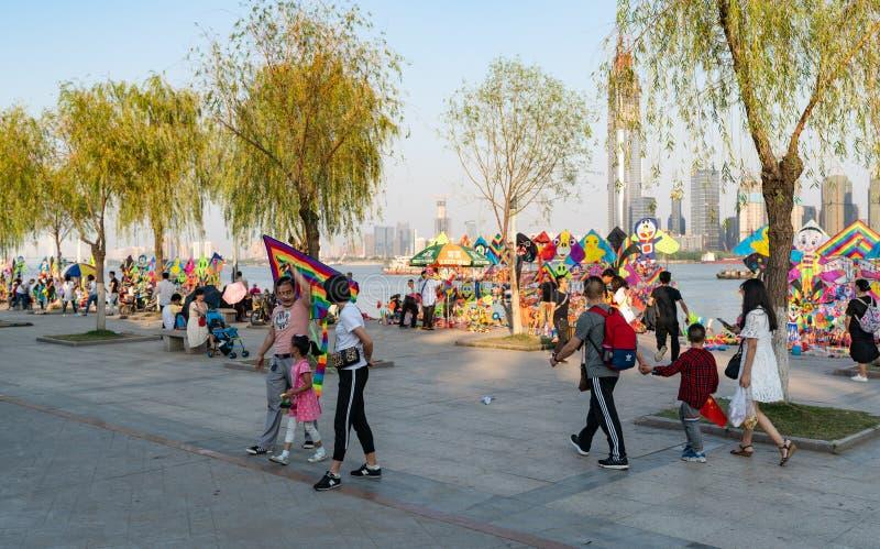 Familia china que lleva a cabo una cometa y paradas de la cometa en el riversi de yangtze foto de archivo libre de regalías