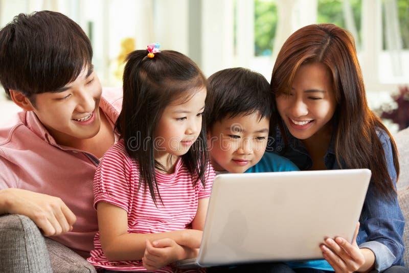 Familia china usando la computadora portátil mientras que se relaja fotografía de archivo libre de regalías
