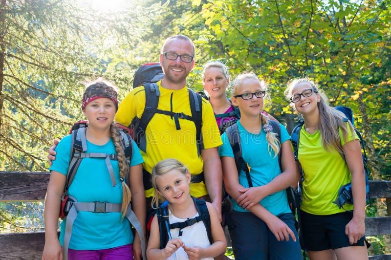 Familia con cuatro niños que caminan en las montañas imagenes de archivo