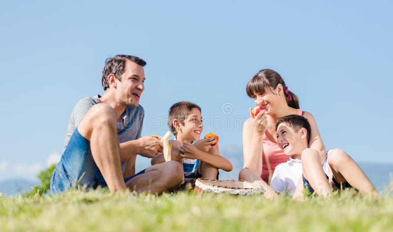 Familia con dos hijos que tienen una comida campestre con las frutas en parque en el summ imagen de archivo libre de regalías