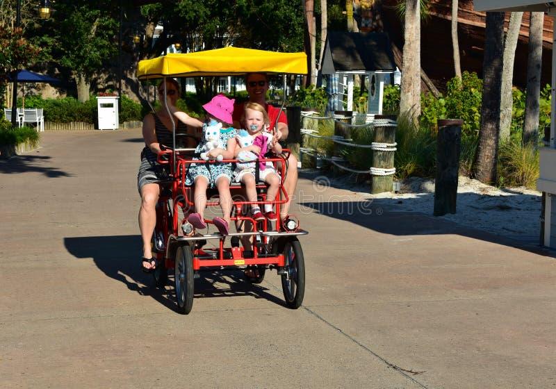 Familia con dos muchachas hermosas, disfrutando de un paseo en la bici de Surrey en el área de Buena Vista del lago imagen de archivo