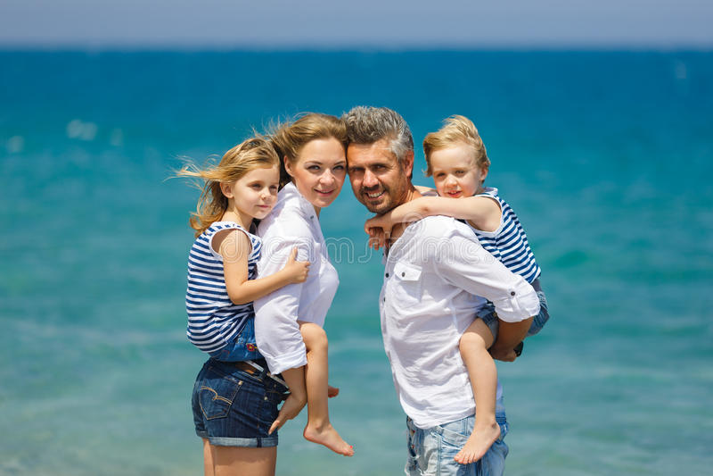 Familia con dos niños en la playa imagenes de archivo