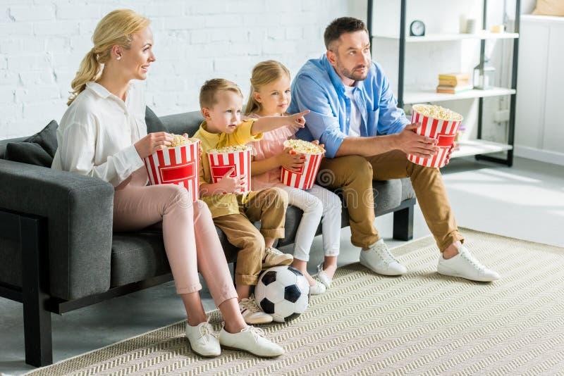 familia con dos niños que comen las palomitas y que ven la TV imagen de archivo libre de regalías