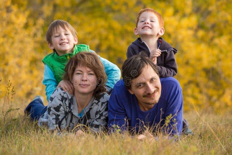 Familia con dos niños que se acuestan en paisaje del otoño imagenes de archivo