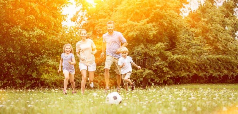 Familia con el balón de fútbol en verano imágenes de archivo libres de regalías