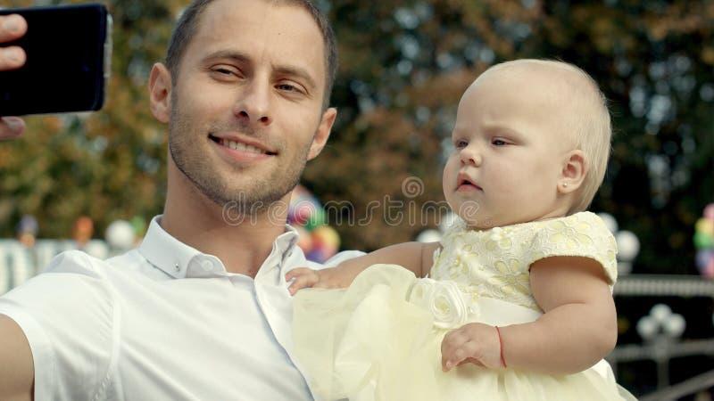 Familia con el bebé en el parque que toma el selfie por el teléfono móvil imagenes de archivo