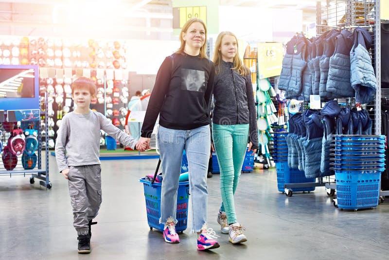Familia con el carro de la compra en tienda de las mercancías del deporte imagen de archivo